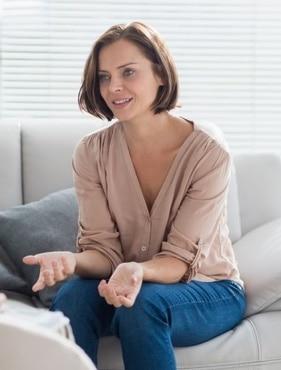Eine Frau auf einem Sofa führt ein Gespräch