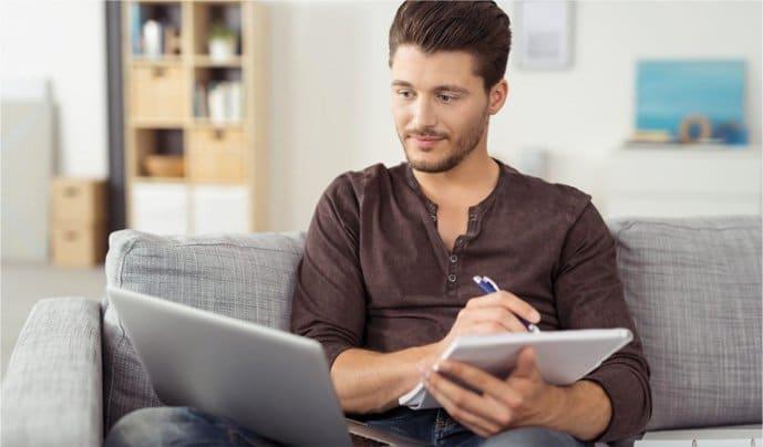 Ein Mann sitzt auf seiner Couch und lernt an einem Laptop